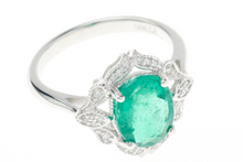 AN EMERALD AND DIAMOND DRESS RING IN PLATINUM