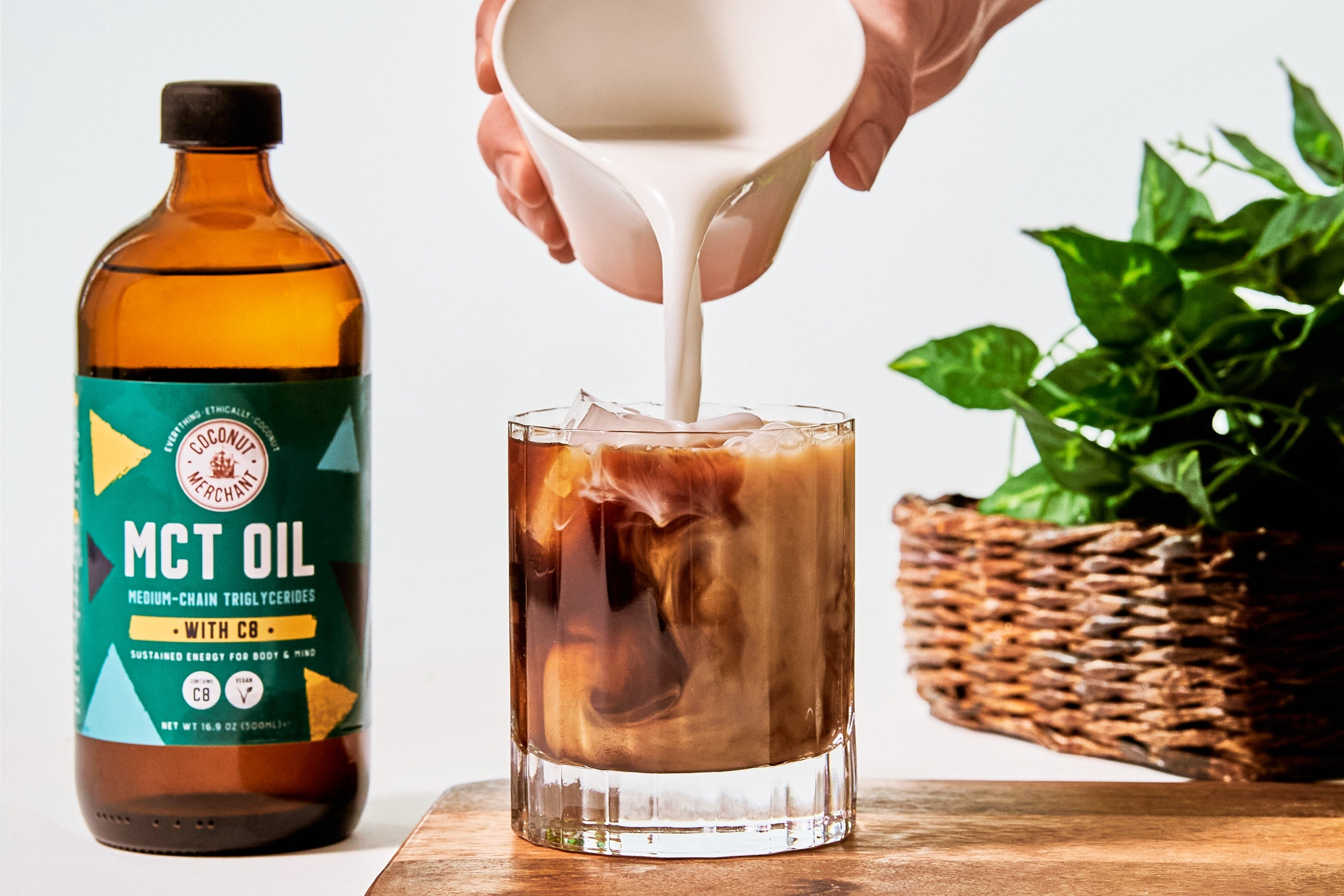 Bottle of MCT oil with someone pouring in coconut milk into a small glass of coffee next to it