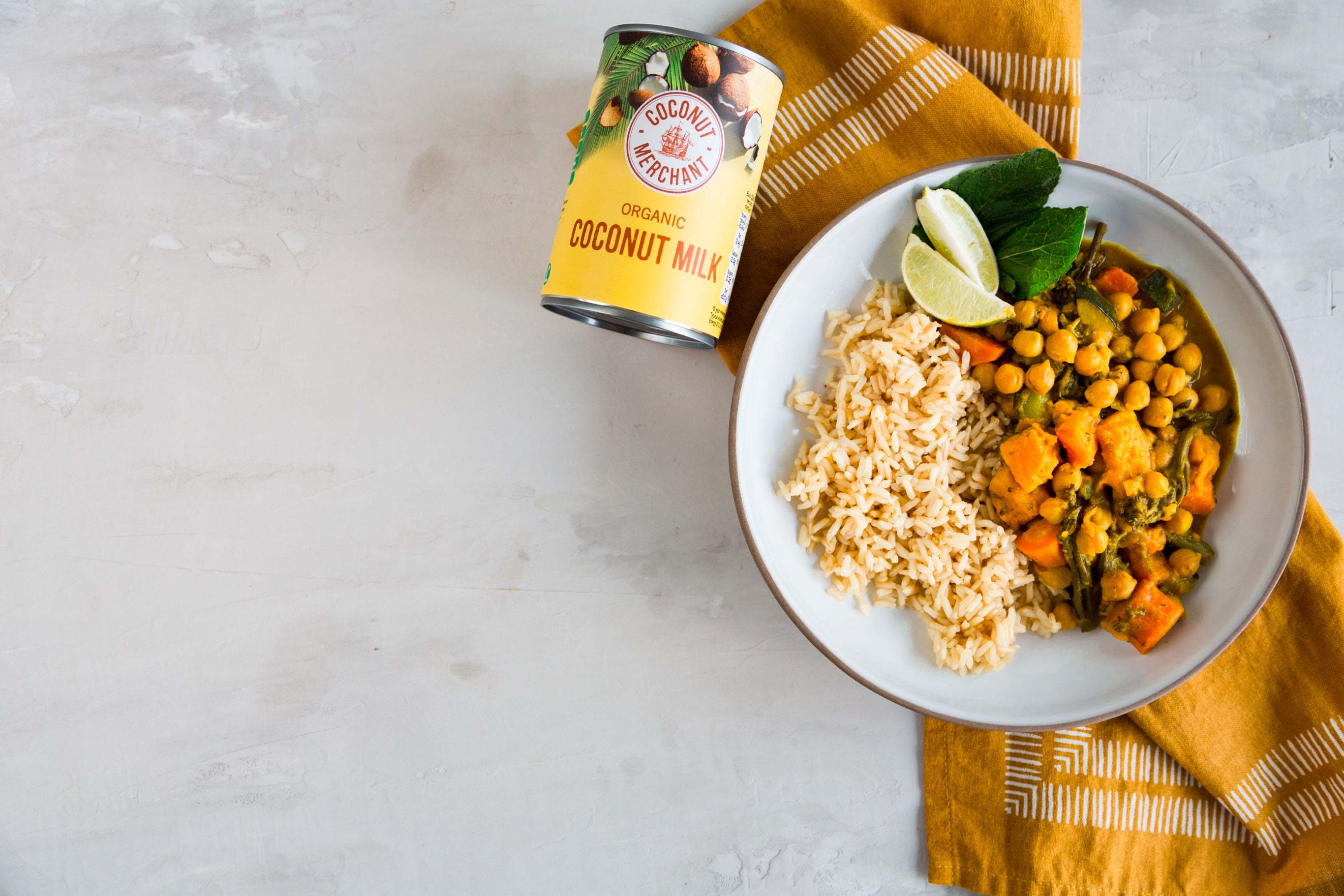 Bowl of rice and vegetable curry with a tin of coconut milk next to it
