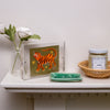 curated shelfie, two webster, tiger artwork, candle, pottery dish, flowers, vase, woven tray