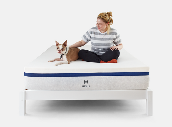 Woman and dog sitting on Helix mattress on Helix white wood bed frame