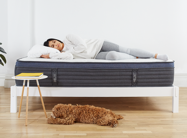 Woman lying on Helix Mattress on Helix White Wood Frame