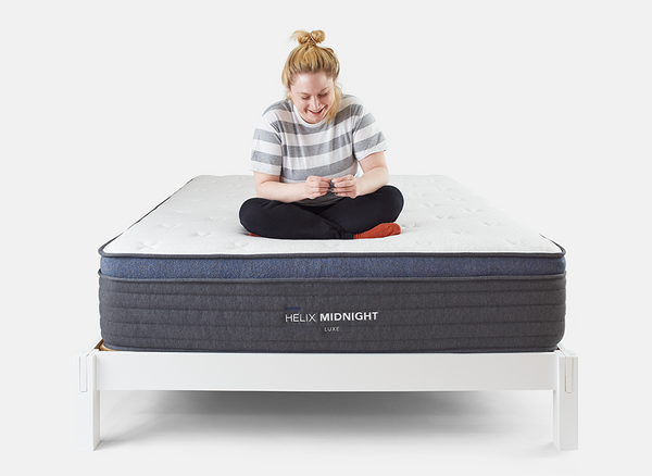 Woman sitting on Helix Luxe Mattress on Helix White wood bed frame