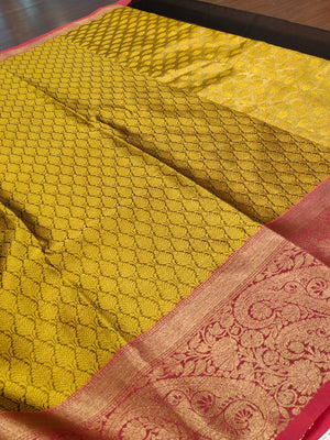 Yellow tanchoi kora saree with pink border and golden zari weaving