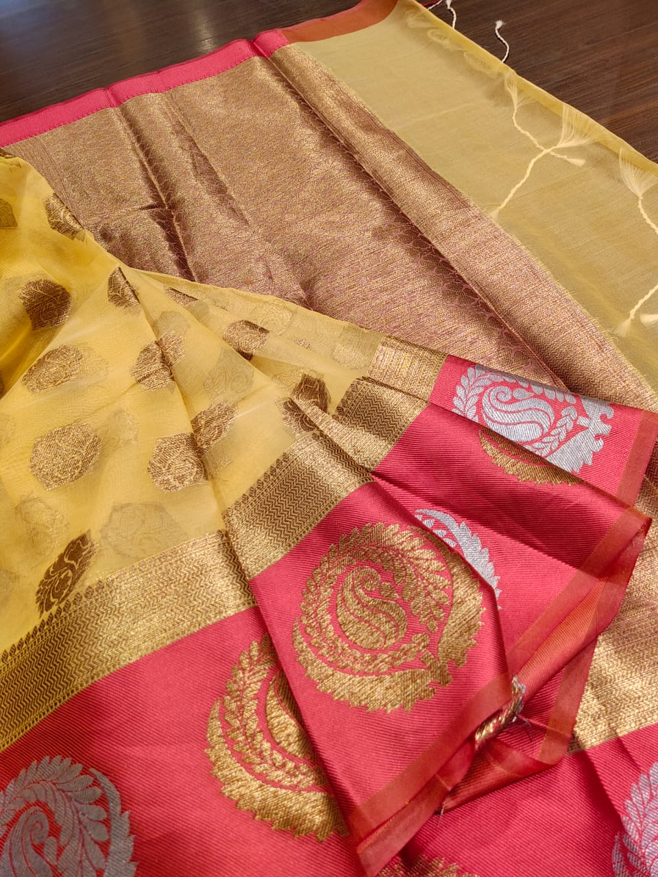Yellow kora saree with pink border and golden butties all over