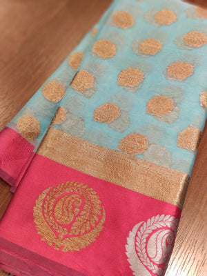 Sky blue kora saree with pink border and golden booties allover