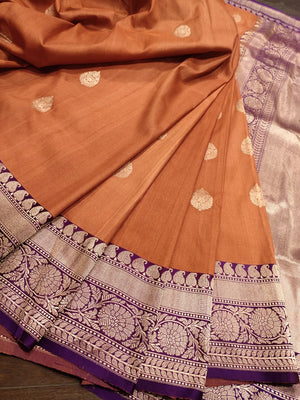 Orange pure silk saree with silver zari weaving and golden booties all over