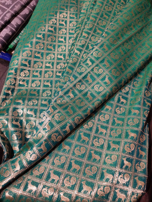 Silk fabric in green with gold zari weaving allover