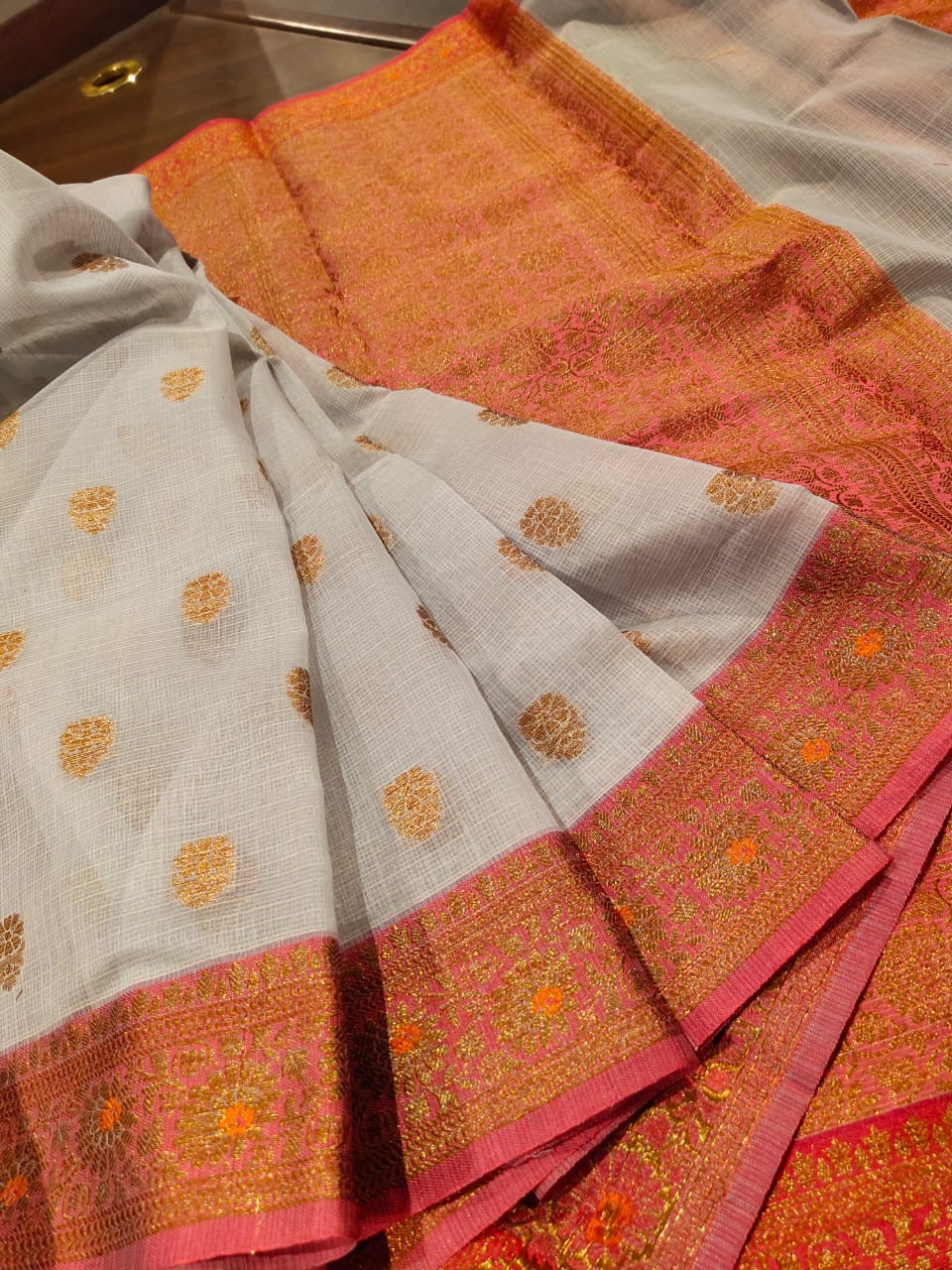 Light grey kota saree with golden zari weaving and booties all over