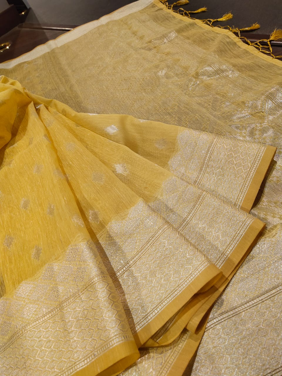 Yellow linen saree with silver zari weaving and booties all over