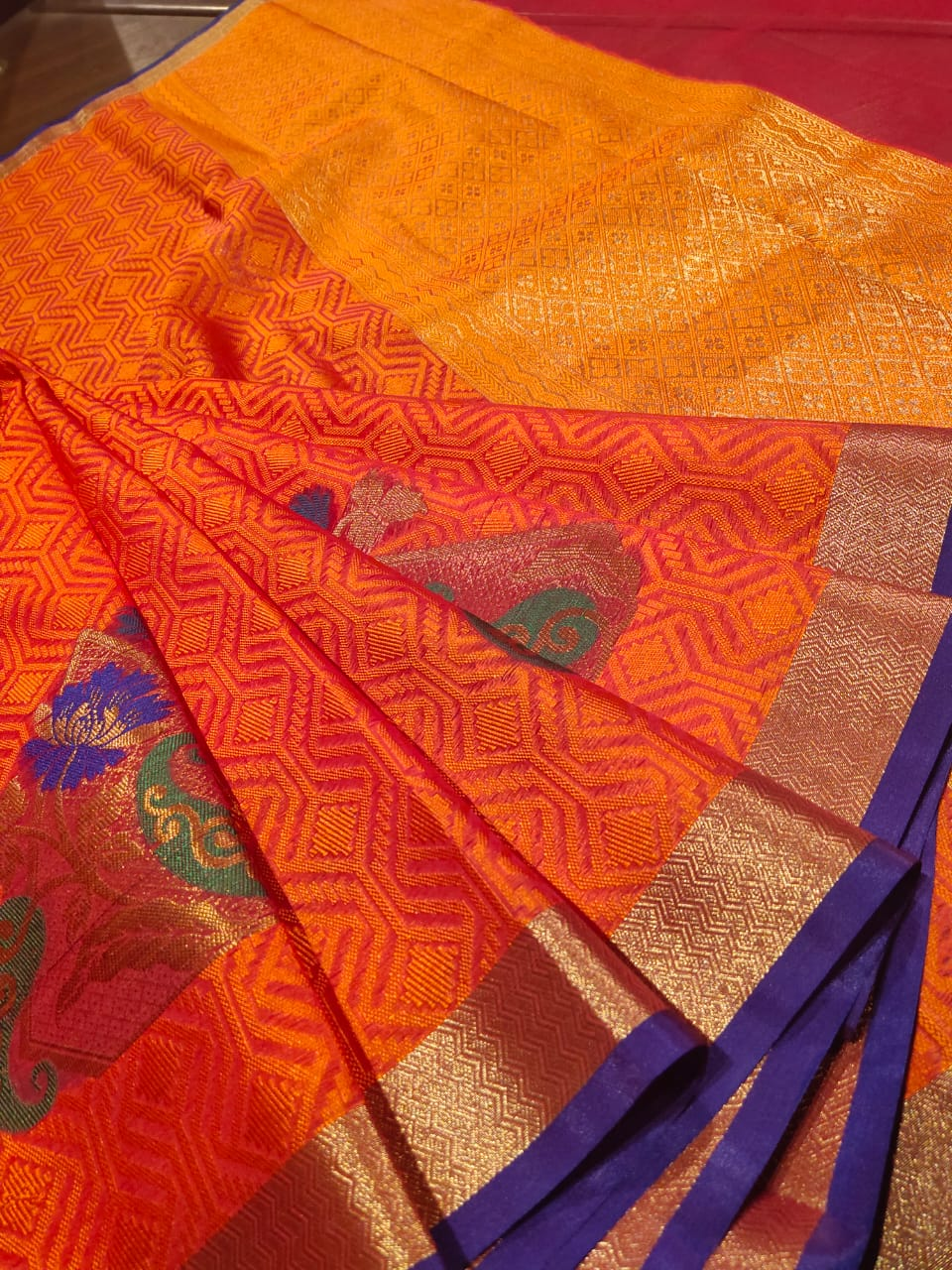 Orange tanchoi kora saree with golden zari weaving and blue border and Multicolor motifs