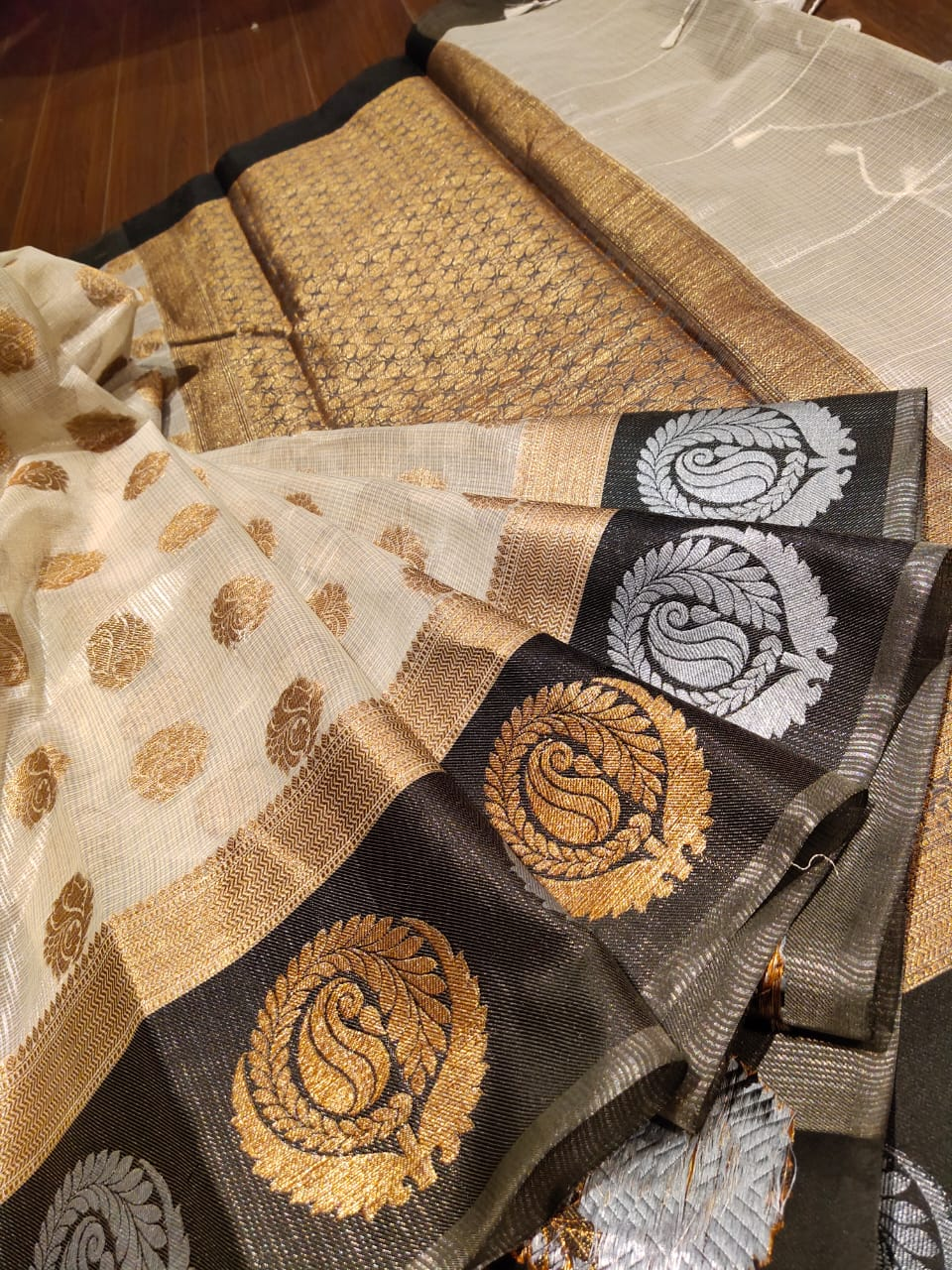 Off white kota saree with golden and silver motifs on black border and golden booties all over