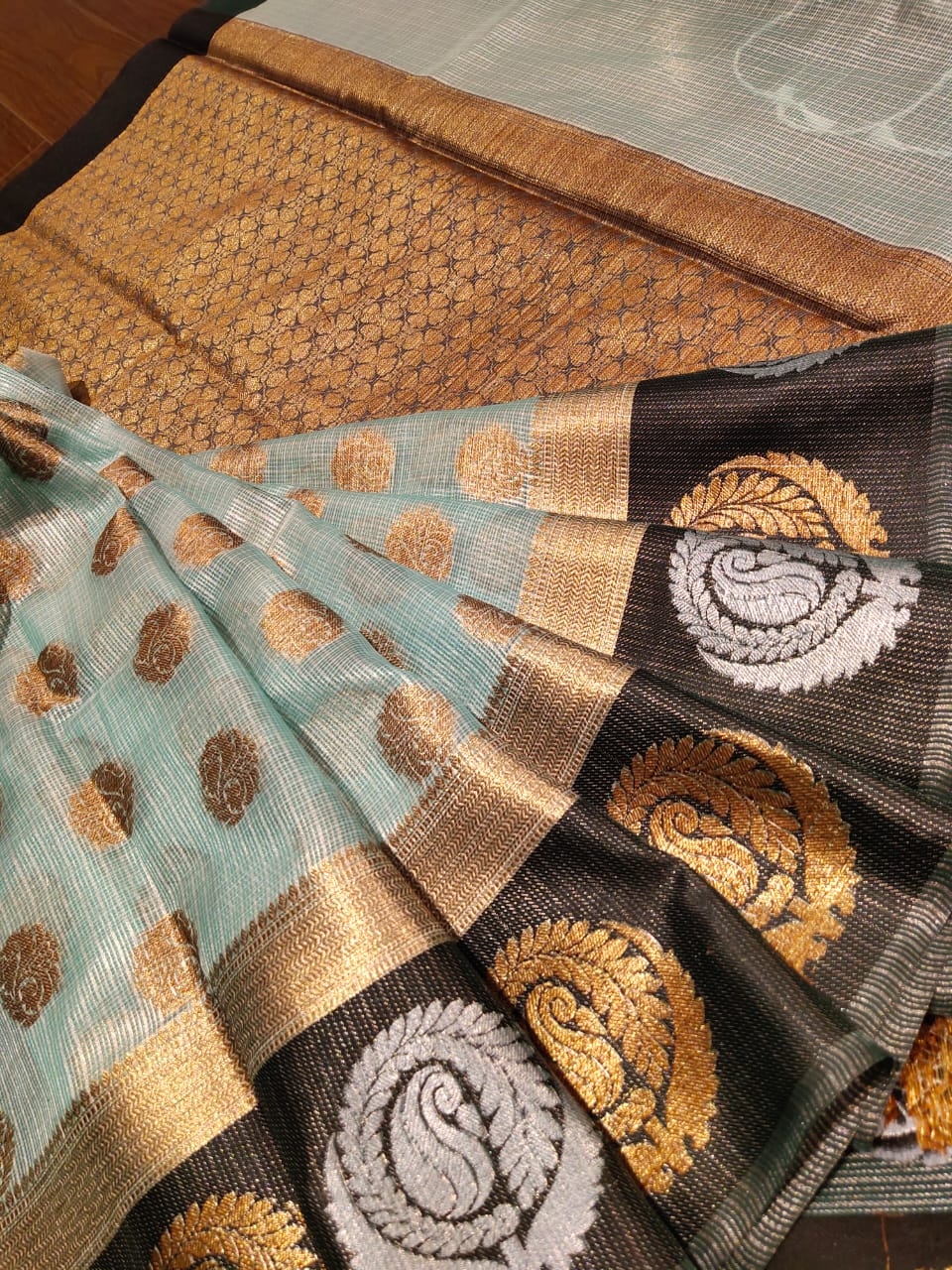 Light sea green kota saree with golden and silver motifs on black border and golden booties all over