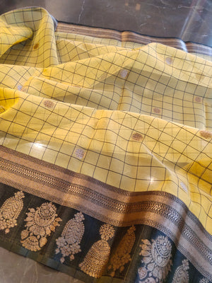 Yellow kora silk saree with black checks all over and golden zari booties