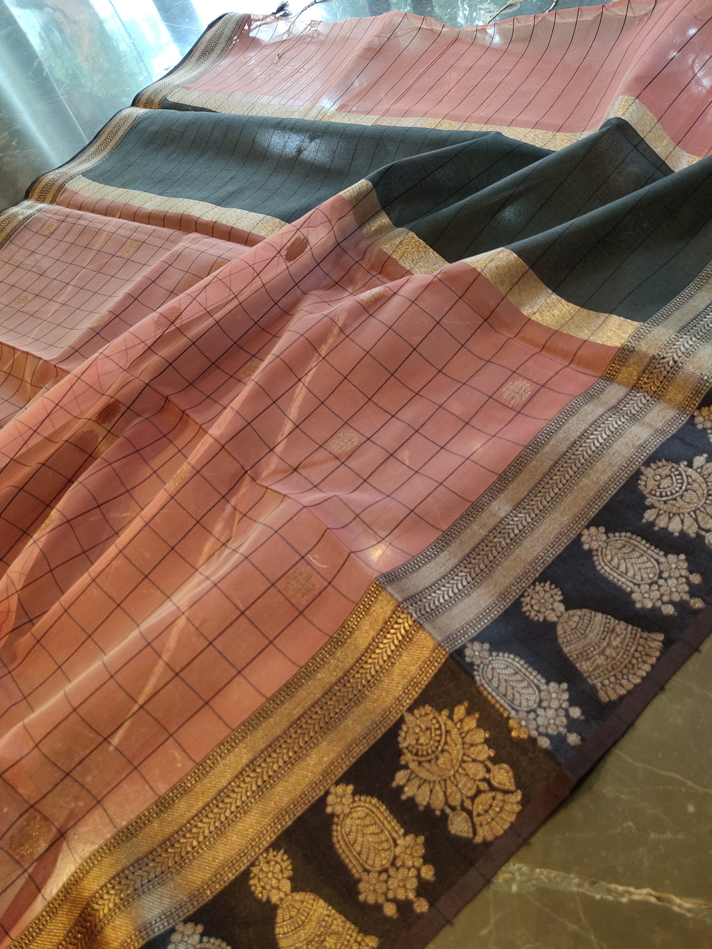 Pink kora silk saree with all over black checks and golden zari booties