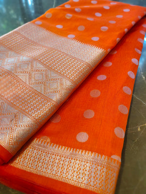 Orange chanderi saree with all over silver zari bootties and silver border