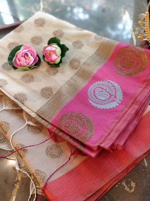 Cream kota saree with silver and golden motifs on pink border and golden booties all over
