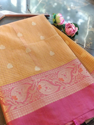 Light orange supernet kota saree with golden zari weaving and pink border and golden booties all over