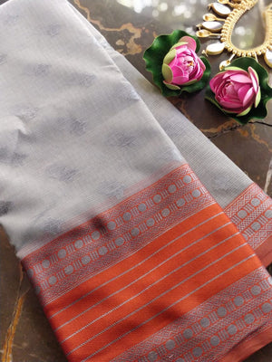 Light grey kota saree with silver zari weaving on orange border and booties all over
