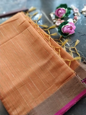 Orange zari linen saree with self strip allover and pink border