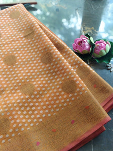 Light orange jute saree with golden zari weaving and golden and white booties all over