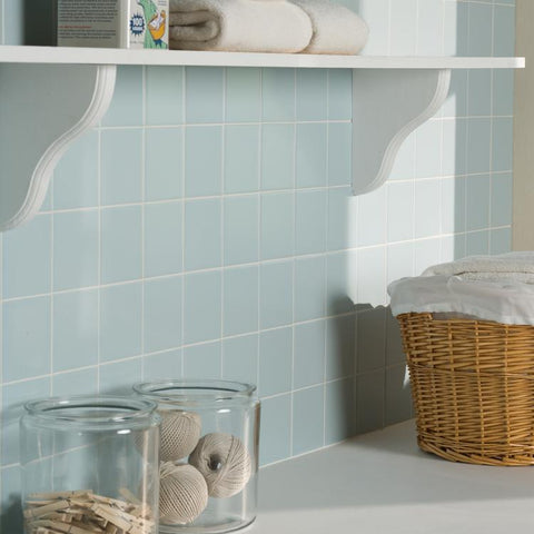 Square, glacier blue ceramic wall tiles shown on laundry room wall, featuring a white floating shelf and a wicker laundry basket
