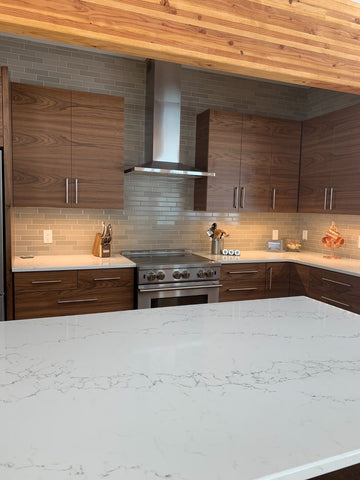 Dolce mocha ceramic tile on the backsplash full wall of a modern kitchen, white veined countertop in foreground.