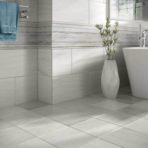 Grey, heathered bathroom tile cut in large squares covering floor and walls