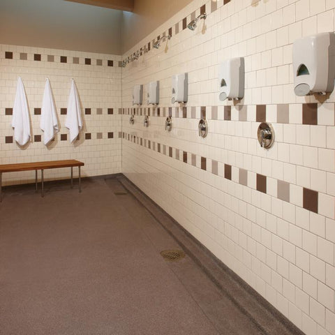 Large public shower space with beige, tan, and brown wall tiles