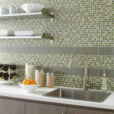 Multi-colored small tiles and gray brick accent lines cover wall over above a modern kitchen counter