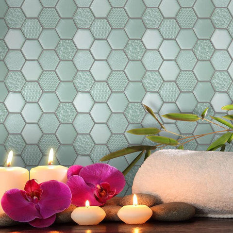 Blue/green hexagonal tiles with various patterns cover wall behind some candles, flowers, and a bath towel