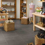 Kitchen store with various kitchen supplies on display, large gray tiles covering floor