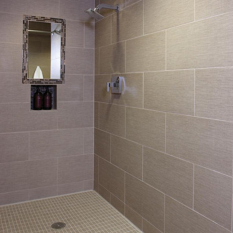 Taupe tiles covering walls of large, walk-in shower with a built-in mirror