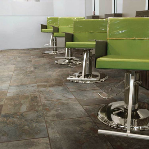 Room with 4 green and silver salon chairs and multicolored slate tile floors and white walls