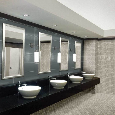 Large public restroom with grey tile walls and floor, big square tile backsplash, 4 sinks, and 4 chrome mirrors