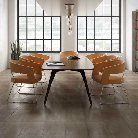Modern dining room with large wood table, funky orange chairs, and brown tiles covering floor