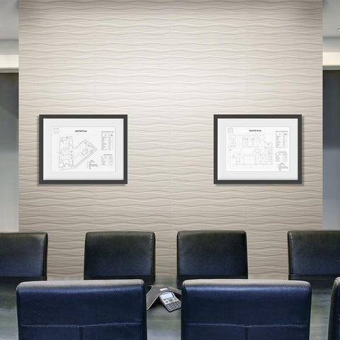 Office conference room with wavy tile accent wall, a long table wtih leather chairs, and a some framed building maps on the wall