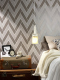grey wall tile in fun pattern on bedroom wall with bed and nightstand