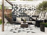Diagonal and field patterns mixed on floor and wall of a modern patio with wood and plants.