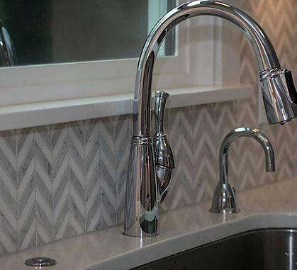 Silver kitchen sink against monochromatic marble tile accent wall in chevron mosaic