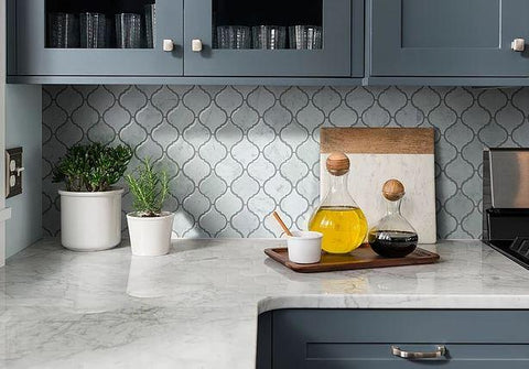 Polished gray lantern mosaic tile gleams in kitchen setting among oils and plants