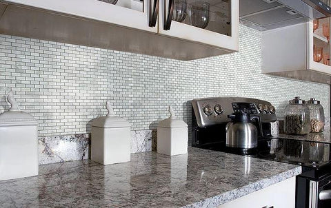 Marble countertops and silver stove against mini brick mosaic tile wall in kitchen