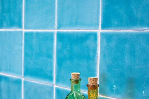 Close up of oceano blue wall tile on a backsplash with oil bottles in front.