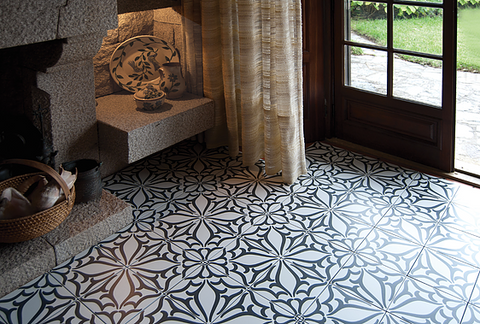 Classic C Noir porcelain pattern tile on the floor of an entryway with open door, curtain, and fireplace.
