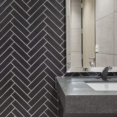 Black matte handmade look wall tile set in herringbone behind a vanity