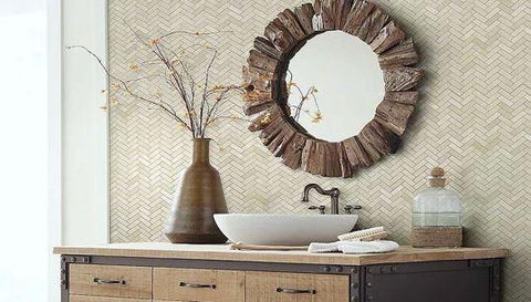 White sink basin, trendy bronze mirror and vase against natural Herringbone mosaic tile wall