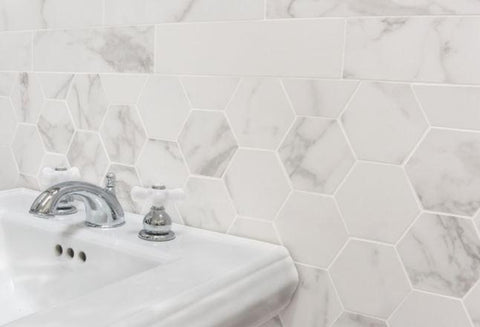 "3x12s and 4"" hexagons in marble-look porcelain installed on a backsplash behind a sink."