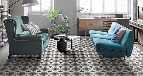 Living room with 2 blue couches, a modern coffee table, and a patterned tile floor