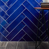 4x16 Gioia Navy colored tile set in a herringbone pattern on a wall close up abutting a wood-look floor.