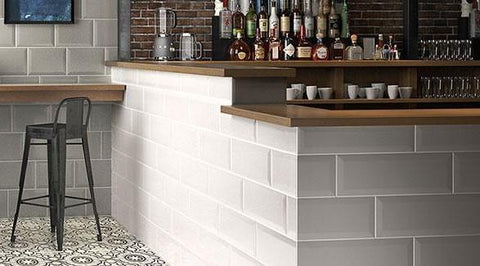 Bar with gray tile brick walls and wooden countertops, liquor bottles behind bar